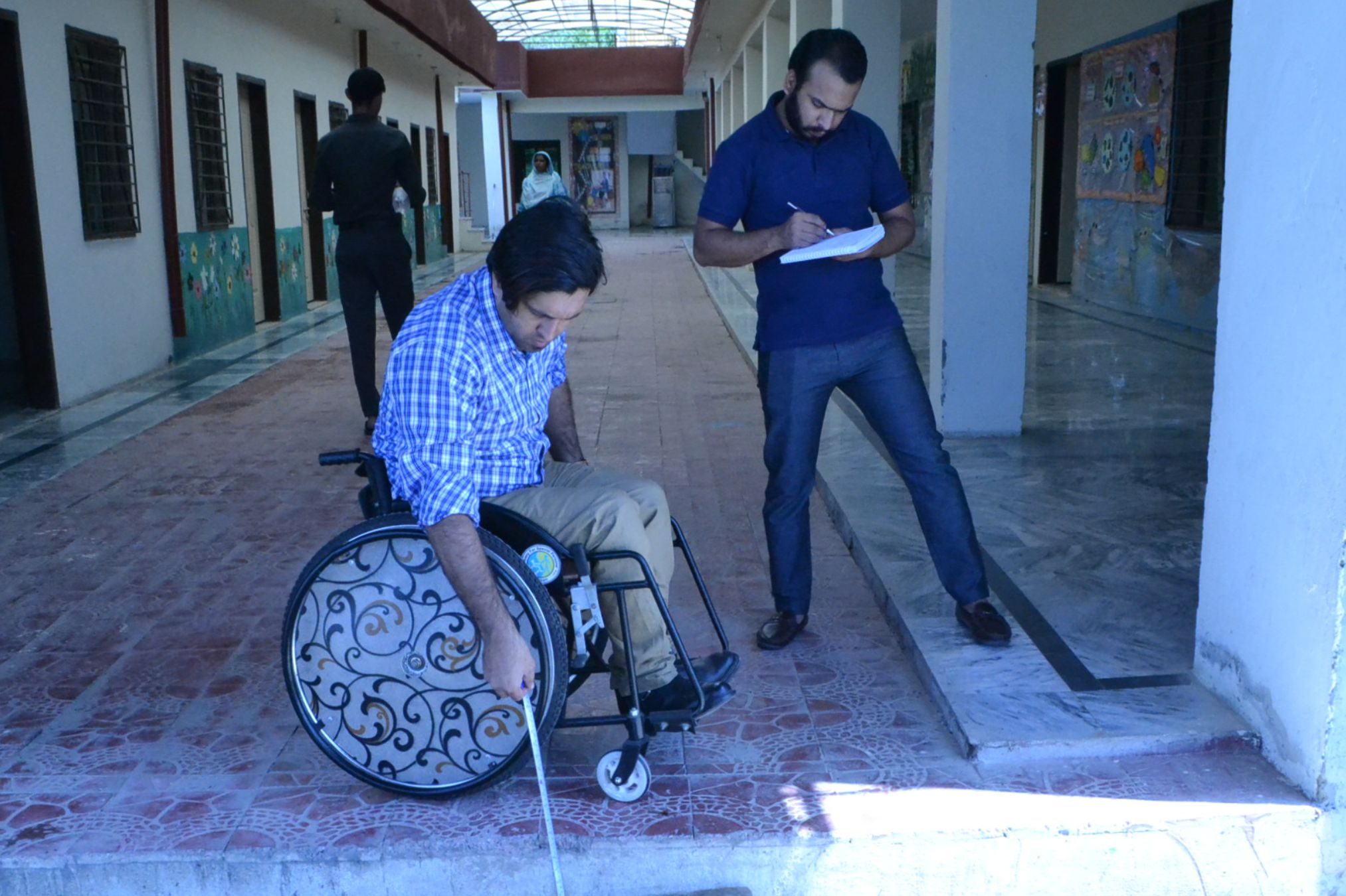 Wheelchair User taking Measurements In accessibility audit of silver oaks school